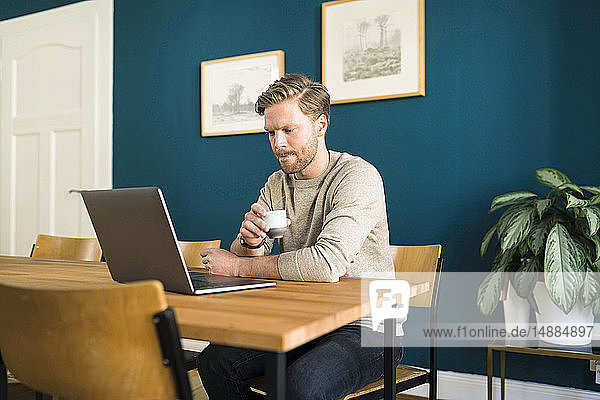 Man working on laptop on wooden table in home office drinking espresso