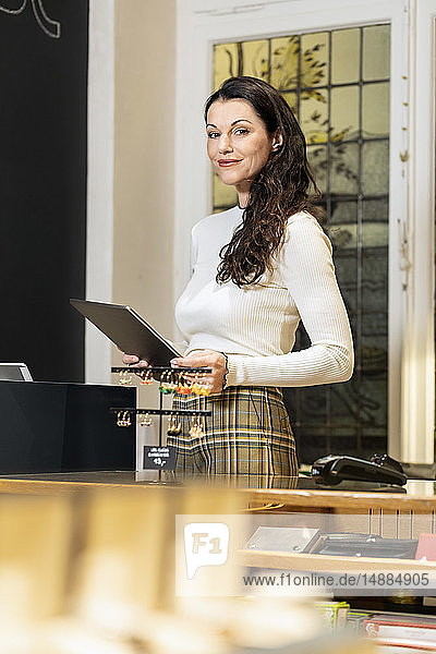Mature woman working in fashion store  using digital tablet