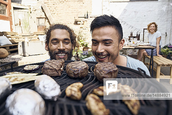 Friends preparing meat for a barbecue in the backyard