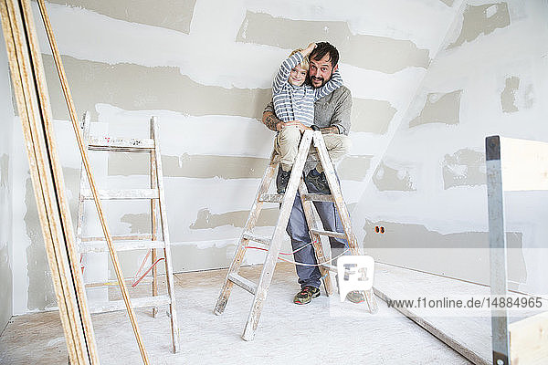 Porträt eines glücklichen Vaters und eines glücklichen Sohnes beim Dachbodenausbau