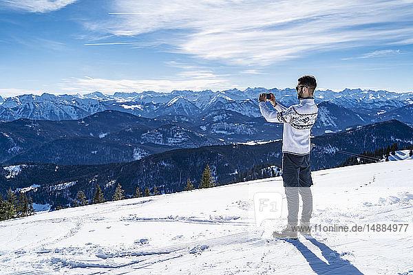 Deutschland  Bayern  Brauneck  Mann im Winter in den Bergen beim Fotografieren