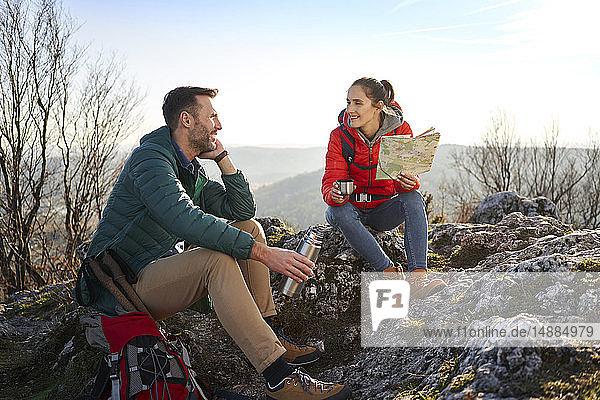 Glückliches Paar auf einer Wanderung in den Bergen bei einer Pause