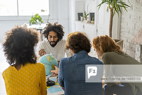Friends meeting to plan vacations  checking map and globe