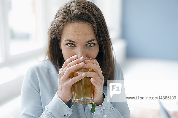 Pretty woman drinking tea from a glass