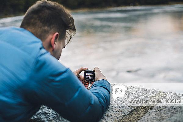 Junger Mann fotografiert einen zugefrorenen See mit einer kleinen Kamera