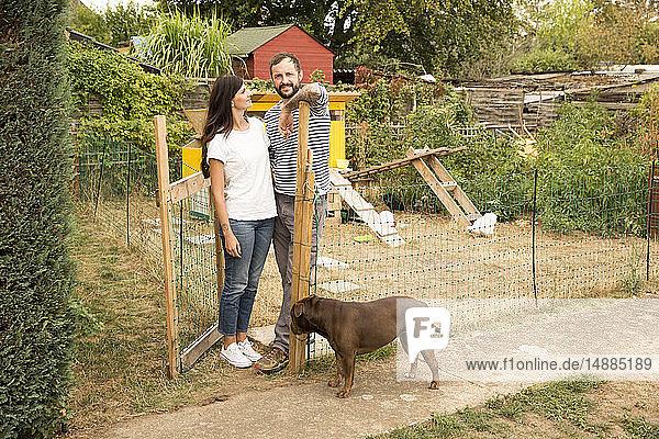 Porträt eines Ehepaares mit Hund beim Hühnerstall im Garten stehend