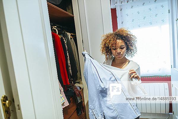 Junge Frau mit lockigem Haar zu Hause betrachtet Kleidung in ihrem Kleiderschrank