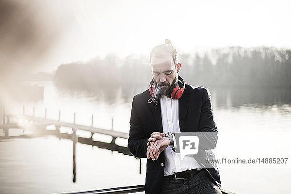 Geschäftsmann steht auf einer Hauspfeife  raucht Pfeife  kontrolliert die Zeit