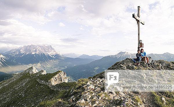 Österreich  Tirol  Mutter und Sohn auf einer Wanderung mit Buch auf dem Gipfel