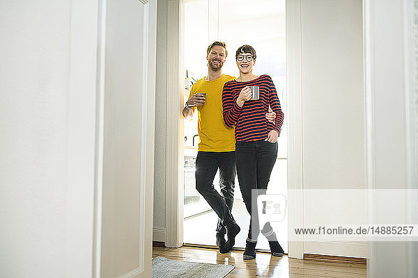 Happy couple leaning in door case in front of their kitchen