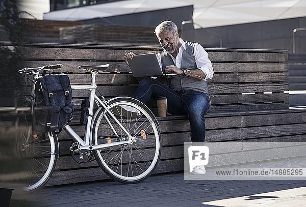 Lächelnder  reifer Geschäftsmann mit Fahrrad  der mit einem Laptop auf einer Bank sitzt
