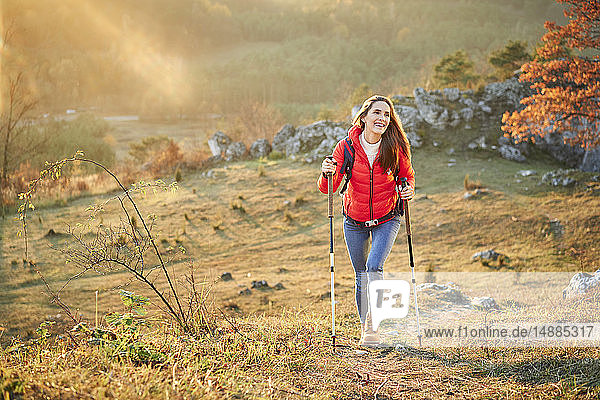 Happy woman walking on trail on a hiking trip in the mountains