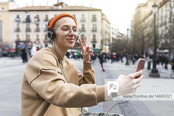 Junge Frau  die sich beim Musikhören ein Selfie nimmt und mit ihrer Hand eine Friedensgeste macht