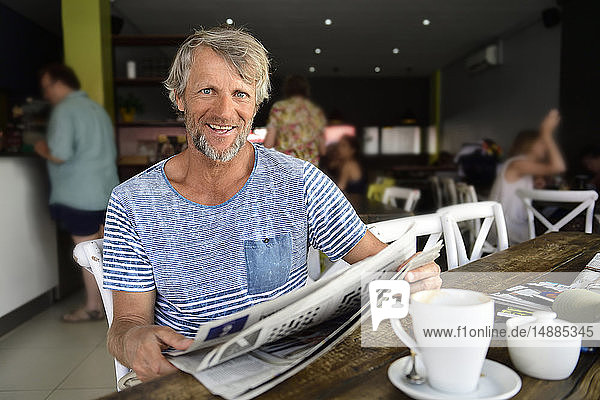 Portrait of smiling mature man sitting in a coffee shop reading newspaper