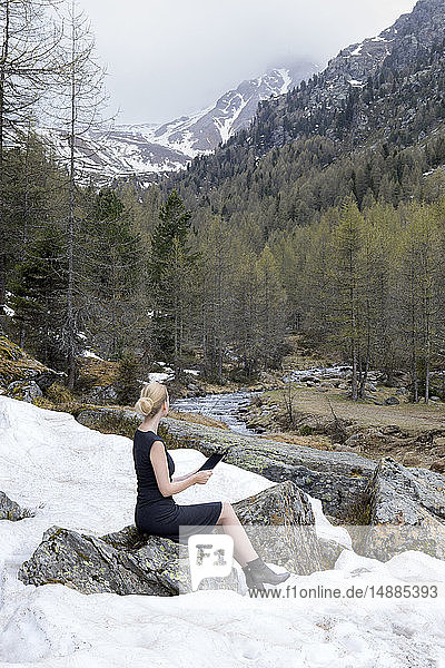 Italy  Alto Adige  Ultental  woman sitting in snow-capped mountain valley using tablet