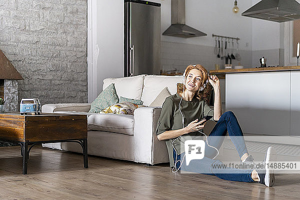 Young woman sitting on floor at home  using smartphone  wearing headphones