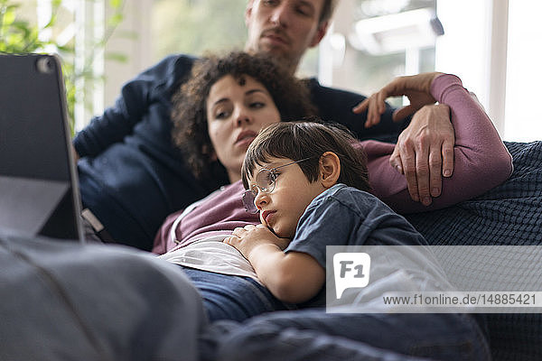 Family lying on couch watching movie on theit tablet