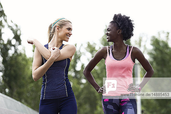 Two sporty young women talking and relaxing after running in the city