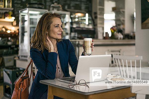 Geschäftsfrau sitzt im Café  isst zu Mittag  arbeitet am Laptop