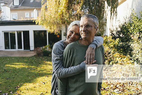 Happy affectionate senior couple hugging in garden
