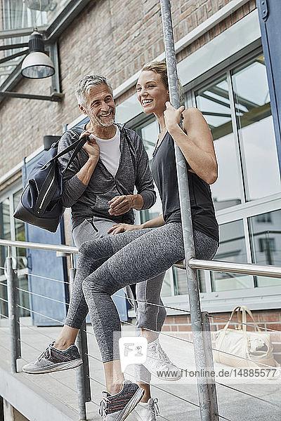 Porträt eines reifen Mannes mit Sporttasche und lachender junger Frau vor der Turnhalle
