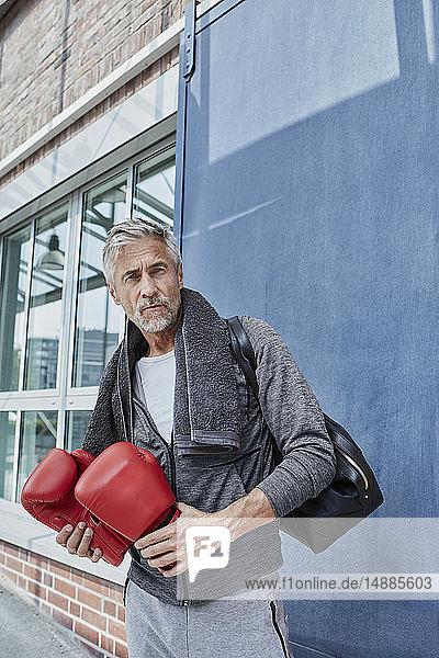 Porträt eines reifen Mannes mit Handtuch  Sporttasche und roten Boxhandschuhen vor der Turnhalle stehend