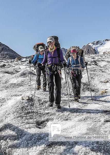 Grönland  Sermersooq  Kulusuk  Schweizer Alpen  drei lächelnde Menschen beim Wandern in verschneiter Berglandschaft