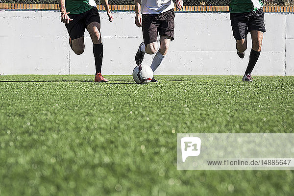 Legs of football players during a match on the field