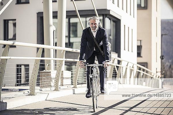 Lächelnder reifer Geschäftsmann mit Kopfhörern beim Fahrradfahren auf einer Brücke in der Stadt