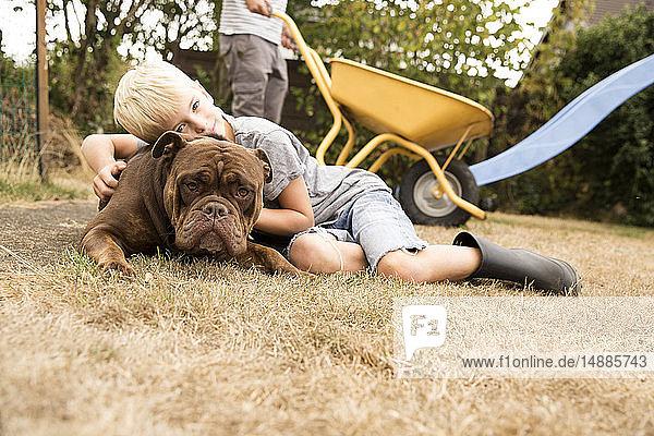 Junge kuschelt mit Old English Bulldog auf Spielplatz im Garten