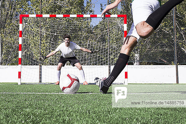 Football player shooting the ball on football field