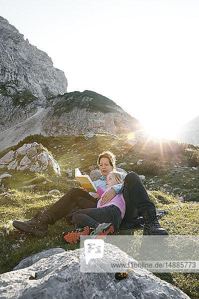 Österreich  Tirol  Mutter und Tochter lesen Buch in Berglandschaft bei Sonnenuntergang