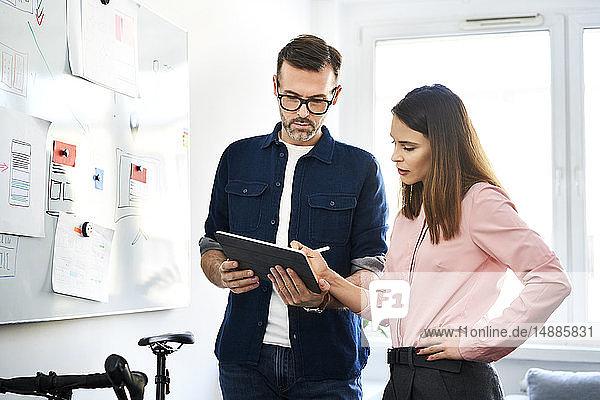 Zwei Kollegen am Whiteboard teilen sich das Tablett im Büro