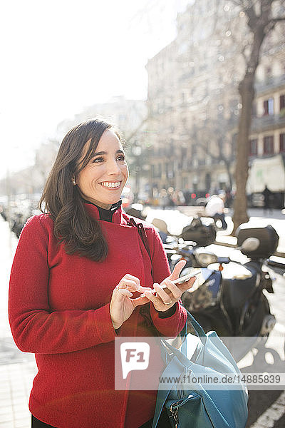 Smiling woman with cell phone in the city
