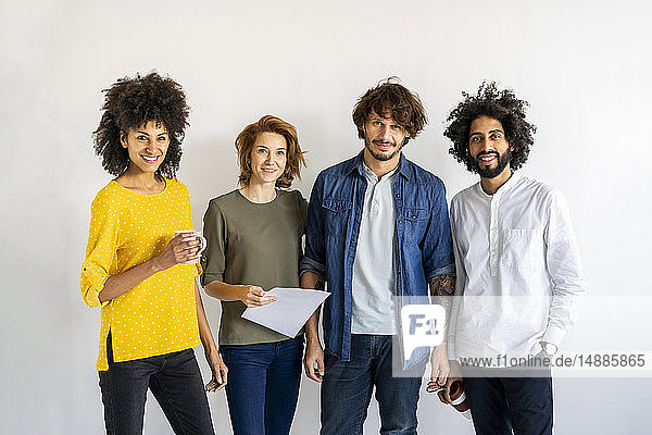 Group of colleagues standing in front of white background