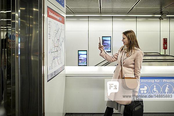Österreich  Wien  junge Frau beim Fotografieren der Karte in der U-Bahn-Station
