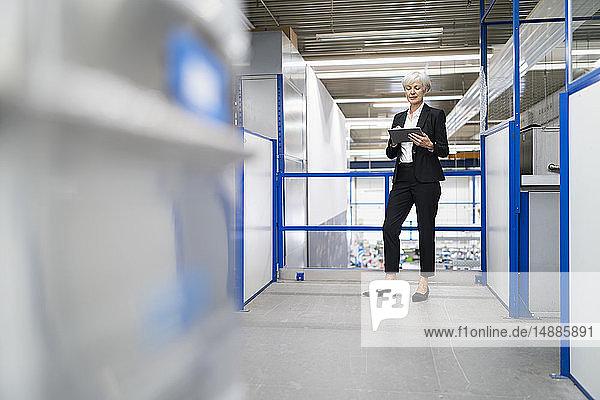 Leitende Geschäftsfrau mit Tabletten in einer Fabrik