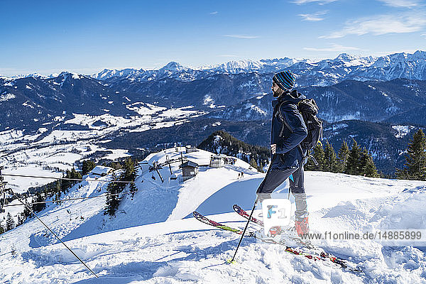 Germany  Bavaria  Brauneck  man on a ski tour in winter in the mountains enjoying the view