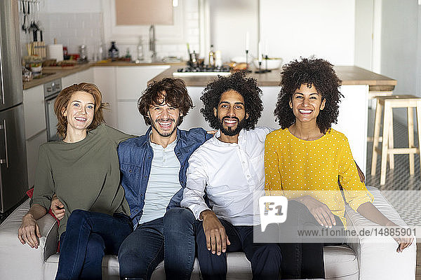 Friends meeting at home  sitting on couch  laughing