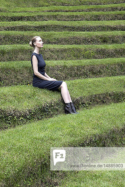 Italy  Alto Adige  Lana  woman sitting on grass-covered steps of natural open air theater