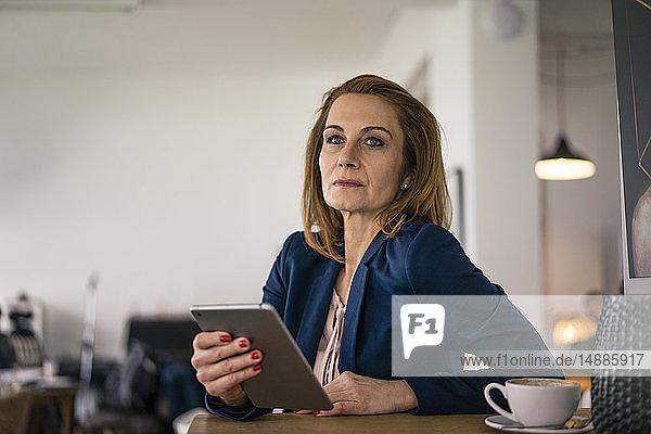 Geschäftsfrau  die in einem Café arbeitet und ein digitales Tablet benutzt