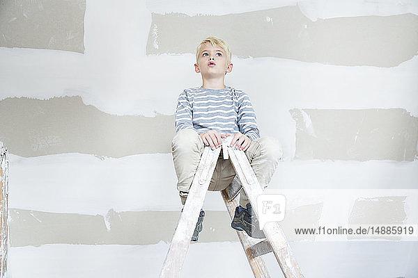 Junge sitzt auf einer Leiter auf dem zu renovierenden Dachboden