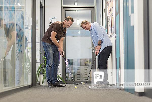 Zwei Geschäftsleute spielen Golf im Amt