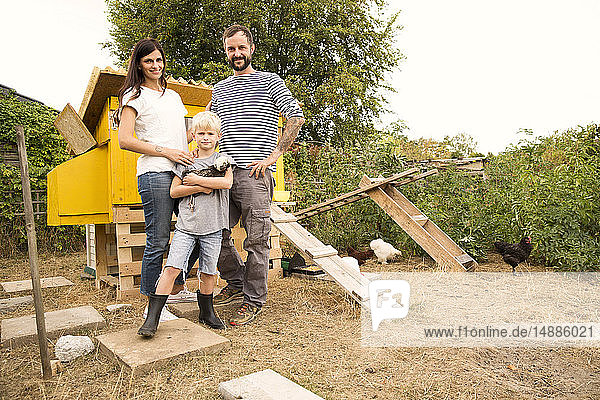 Porträt einer selbstbewussten Familie mit polnischem Huhn im Hühnerstall im Garten