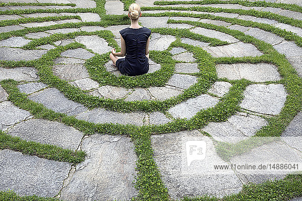 Italy  Alto Adige  Lana  woman sitting in natural open air maze meditating