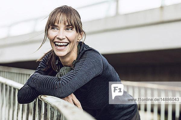 Sportliche Frau mit Kopfhörern  die ihr Fitnesstraining im Freien absolviert