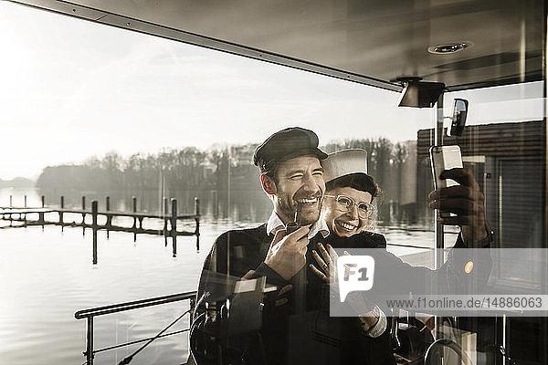 Kollegen  die auf einem Hausboot arbeiten und sich selbst als Matrose und Kapitän nehmen