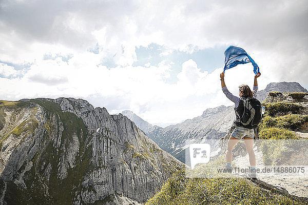 Österreich  Tirol  Frau auf einer Wanderung in den Bergen mit Tuch in der Hand