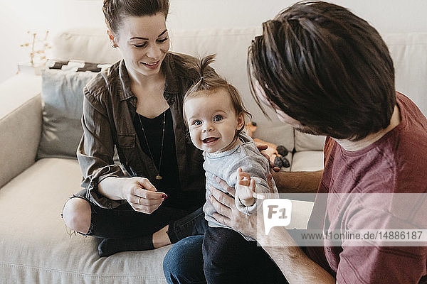 Glückliche Familie mit Mädchen zu Hause im Wohnzimmer