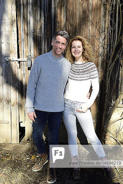 Smiling couple standing in front of wooden shack